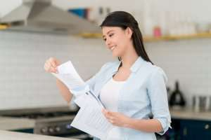 Girl smiling at paperwork– The truth behind Warranties - Fort Myers - Sunset Air & Home Services