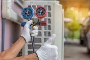 AC contractor holding equipment with thumbs up-Sunset Air and Home Services-Fort Myers-300x200jpg