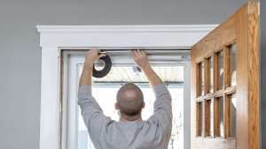 Man using weatherstripping around doors--7 ways to extend the life of your AC part 2 of 2-Sunset Air and Home Services–Fort Myers-300x169jpg
