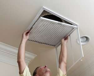 Man changing air filter-Why is my AC turning on and off Part 1-Sunset Air and Home Services-Fort Myers-300x244jpg