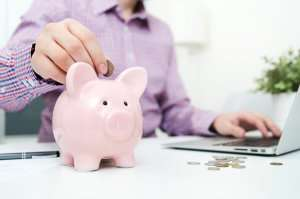 Man placing money in a piggy bank-Which is best-Sunset Air and Home Services-Fort Myers-300x199jpg