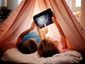 Mom and daughter looking at ipad in homemade fort-AC Fan On or Auto-Which is best-Sunset Air and Home Services-Fort Myers-300x225jpg