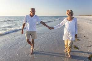 Elderly couple walking on beach holding hands-7 To Dos when returning to Florida-Sunset Air and Home Services-Fort Myers-300x200pg
