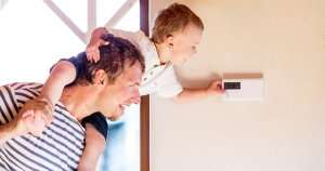 dad and son adjusting thermostat-Sunset Air and Home Services-Fort Myers-300x158jpg