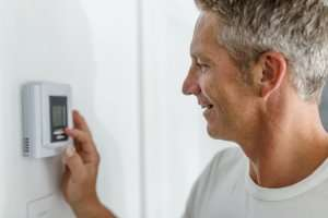 man adjusting thermostat-AC Tips for any Season Part 3 of 3-Sunset Air and Home Services-Fort Myers-300x200jpg