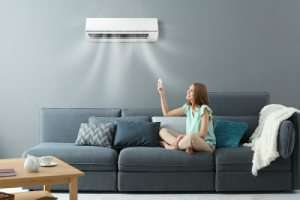Mini split unit in living room with lady on couch-Mini split efficiency-Sunset Air and Home Services-Fort Myers FL-300x200