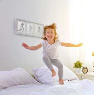 Happy little girl jumping on the bed-Spring Forward with 9 Safety Checks-Sunset Air and Home Services-Fort Myers FL-300x305jpg
