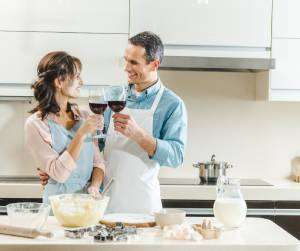 Couple toasting in kitchen-Sunset Air and Home Services-7 Ways to Save Money This Summer-Fort Myers-300x323