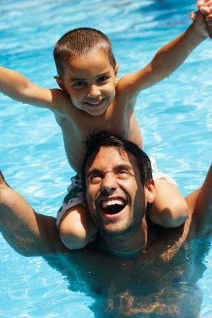 dad and son at pool-Is Regular AC Maintenance Needed-Sunset Air and Home Services-Fort Myers-300x450