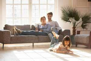 Family Relaxing In Living Room In Front Of Sunny Window-Controlling Humidity In SW Florida-Sunset Air and Home Services-Fort Myers-300x200